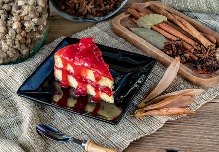 Slice red cherry cake on black plate