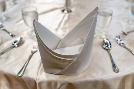 White restaurant napkin with fork and spoon on white table