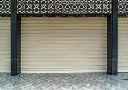 Old beige roller shutter door with black pole and concrete tiles floor
