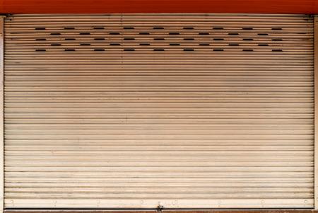 Old rusty beige roller shutter door with concrete floor