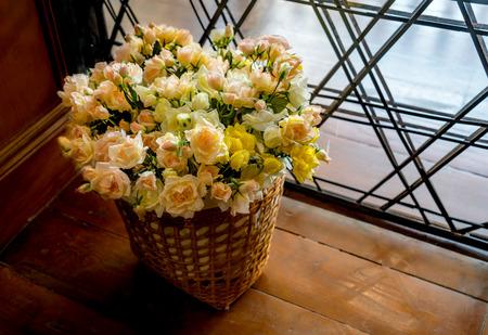Flowers in bamboo basket on wooden floor