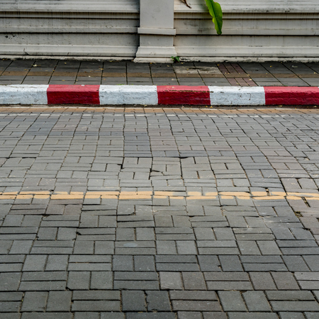 Concrete block road with red and white curb Reklamní fotografie