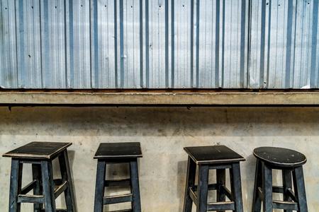 Mini wood stool on concrete wall  background