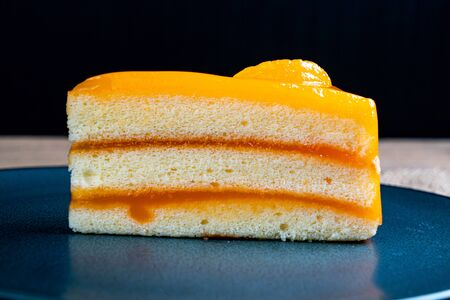 Piece of orange cake on black ceramic plate