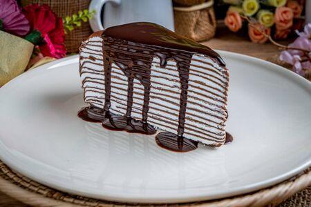 Piece of Chocolate crepe cake on white ceramic plate
