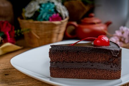 Piece of Chocolate cake with red cherry on white ceramic plate