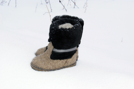 valenki: Russian traditional winter felt gray kids boots valenki with fur standing on the snow. Snow poured shoes.