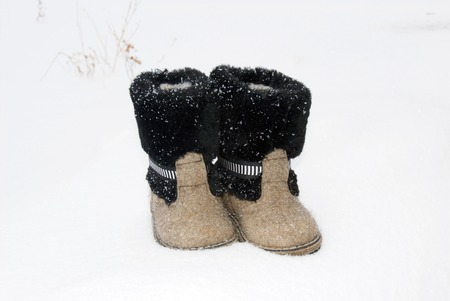 Russian traditional winter felt gray kids boots valenki with fur standing on the snow. Snow poured shoes.
