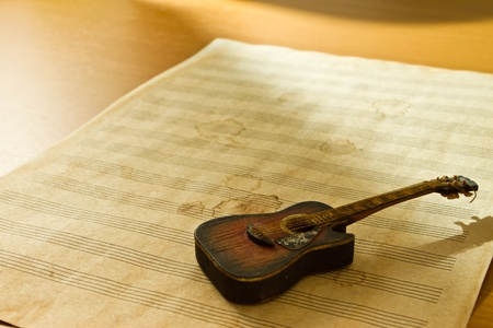 Small guitar on old music sheet photo