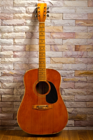 Vintage guitar on sand stone wall Stock Photo
