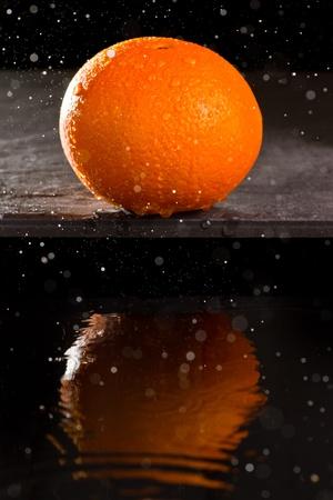 Navel orange with spray tn the air