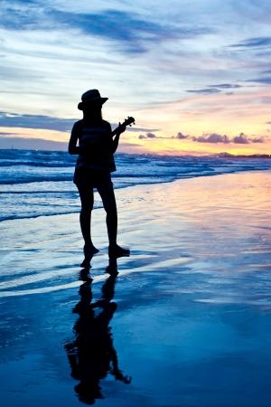 Women playing ukulele on the sunset beach