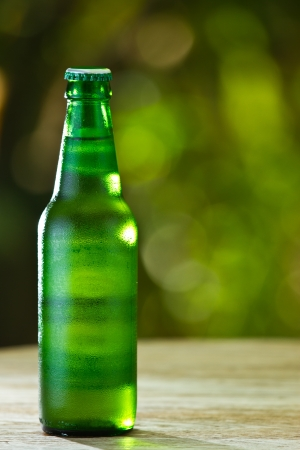Green bottle of beer in nature photo