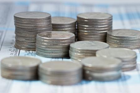 fondos negocios: Pila de monedas sobre el informe de mercado de valores Foto de archivo
