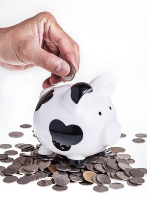 Saving Piggy bank and hand with coin
