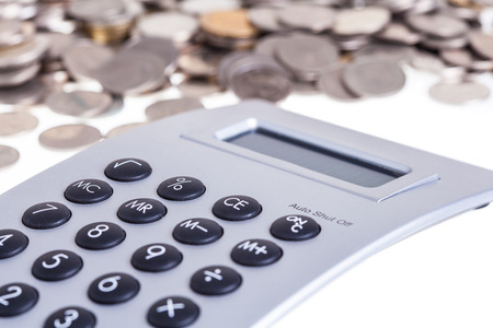 Coins and calculator on isolated white