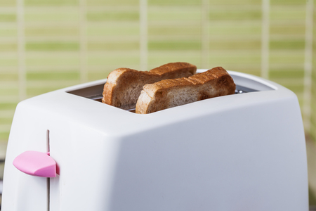 Toast and pink Toaster on green ceramic tile