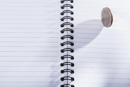 Coin on empty notebook on isolated white background photo