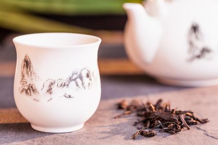 Chinese tea set on black stone with bamboo leaf