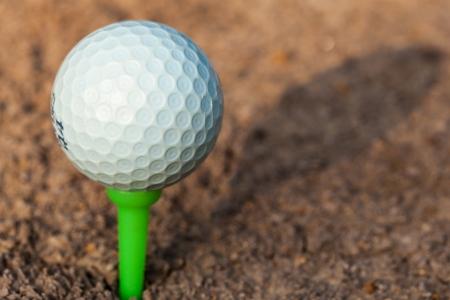 Golf ball on green tee Stock Photo