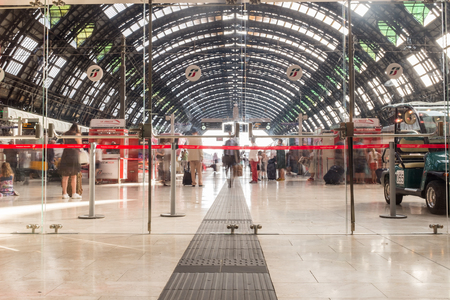 MILAN, ITALY, JULY 9, 2015: Passengers walking around at Milano Centrale - The main railway stration of Milan, Italy.