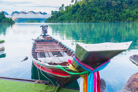 Floating houses at Ratchaprapa dam with wooden boat, Khao sok national park, Thailand.