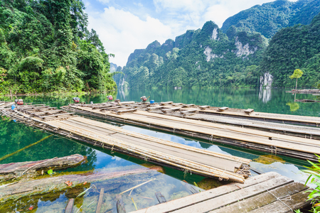 The Floating bamboo raft and Long tail boat on water at Ratchaprapha Dam at Khao Sok National Park, Suratthani Province, Thailand.