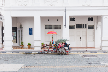 The driver sleeping in his tricycle, parking infront of ancient building, Georgetown, Penang, Malaysia