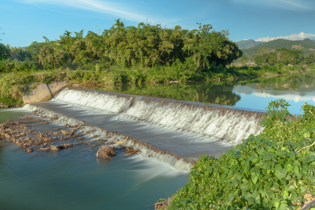 A concrete weir blocks the river to store water for agriculture and consumption. Nan province, northern Thailand