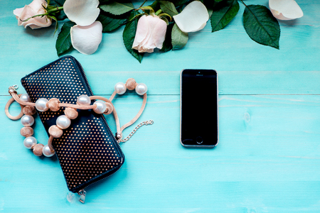Spring background layout on a blue wooden background with flowers and rose petals phone purse and beads accessories on a wooden background 免版税图像
