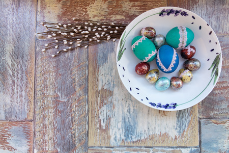 On the old wooden shabby table a dish of metal with painted in a different color Easter eggs chicken and quail and Golden blue green purple feathers, willow