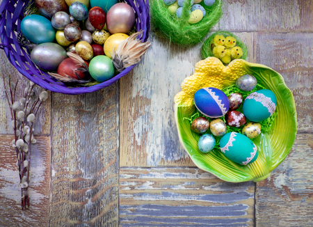 On the old wooden shabby table a dish of metal with painted in a different color Easter eggs chicken and quail and Golden blue green purple feathers, willow and chickens with rabbit Stok Fotoğraf