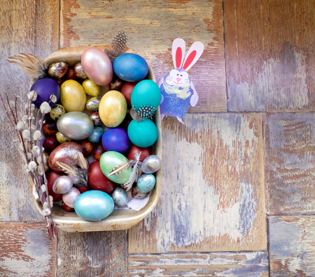 On the old wooden shabby table a dish of metal with painted in a different color Easter eggs chicken and quail and Golden blue green purple feathers, willow and rabbit