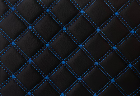classic black leather Mat with straight blue stitching soft leather for machine with textured pattern concept background fabric business Reklamní fotografie