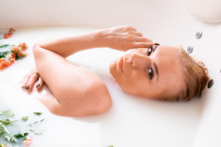 young woman in bath with milk and small coral roses. the girl takes a bath for rejuvenation and care of the body, skin, face and figure. concept beauty, health 写真素材 - 124977167