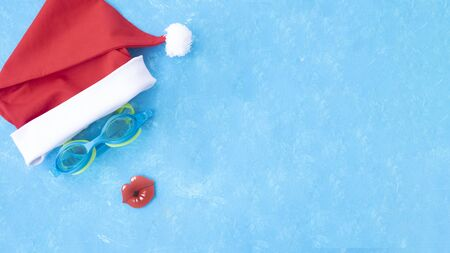 Banner. Hat of Santa Claus with goggles for swimming and a red lips. Christmas vacation, sandals and swimming glasses by water, slippers and pool goggles near swimming pool