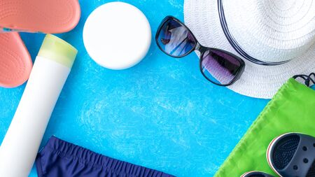 Banner summer vacation concept, accessories for summer travel flay lay on light blue background with a hat, black and blue sunglasses, sunscrin care circle cream and swimming trunks, sandals with copy space for text