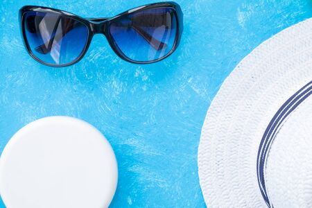 Bottle of sunscreen cream or lotion with a sunglasses flat lay on the blue background with copy space. Spf summer skin protect. Stok Fotoğraf - 129146934