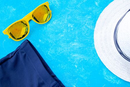 Summer Time concept. Leave space for adding your content or text. Sunny time vacation concept, accessories for summer travel flay lay on light blue background with a hat, black and blue sunglasses, sunscrin care circle cream and swimming trunks, sandals with copy space for text