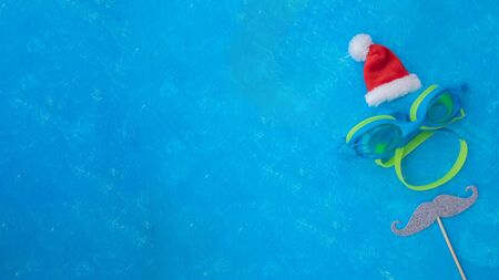 Happy New Year 2020 santa hat on blue swimming pool background with space for your text. Fit swimmer training by himself against new year fresh start