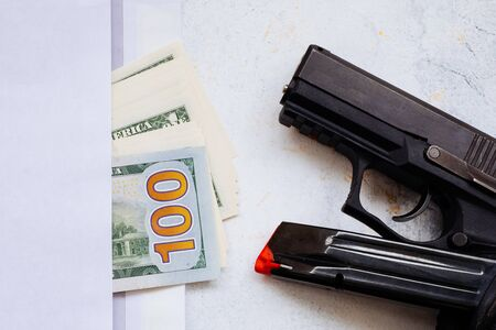 Money for murder. Black gun on American dollars background. Military industry, war, global arms trade, weapon sale, contract killing and crime concept