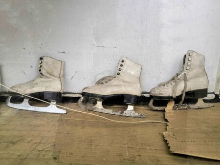 vintage pair of women ice skates hanging on a wooden wall. concept winter