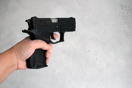 Woman pointing a gun at the target on a gray background Stock Photo