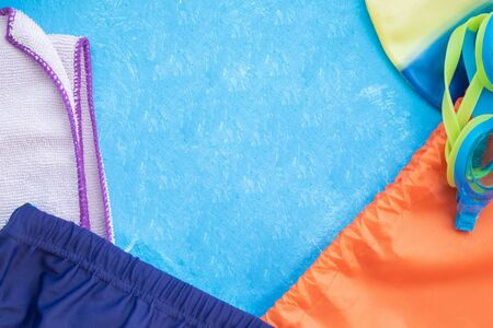 layout on a bright blue background with orange backpack blue swimming goggles cap, swimming trunks, towel and flip flops Concept adult and children swimming in the pool, sports