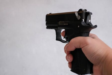 a pistol 9mm, in the hands of women, concept as correctly keep a pistol on training. the index finger is not on the trigger, but along the barrel. 9x19 9mm LUGER caliber pistol rounds. Glock perfection technology Banco de Imagens