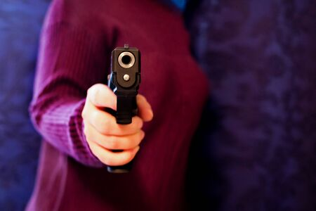 a pistol 9mm, in the hands of women, concept dangerous and beautiful criminal girl with gun on grey wall. 免版税图像