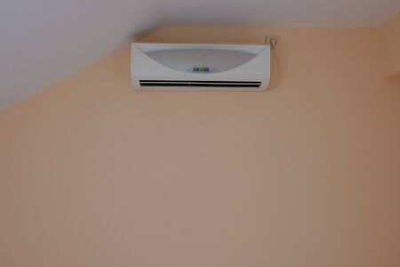 air conditioning on the wall with a sloping roof. Air conditioner inside the room with remote controller Stok Fotoğraf