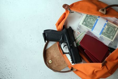 The gun is on the money with your passport, wallet and ammunition. gun passport money. the concept is to escape from the country to lay low and escape from prosecution after Soberania crimes. Stok Fotoğraf