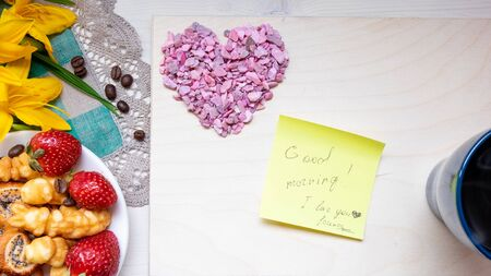 Valentine's day strawberry cookies hearts with coffee, with yellow flowers on a napkin, Notepad with a pen, a note with the text Good morning, I love you happy holiday mother woman Easter Stok Fotoğraf