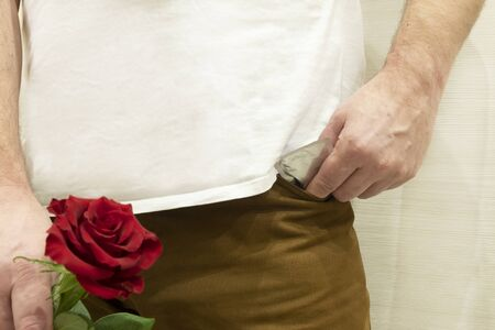 romantic date night in a hotel room, a guy with a red rose, and a condom. Standard-Bild - 139995682